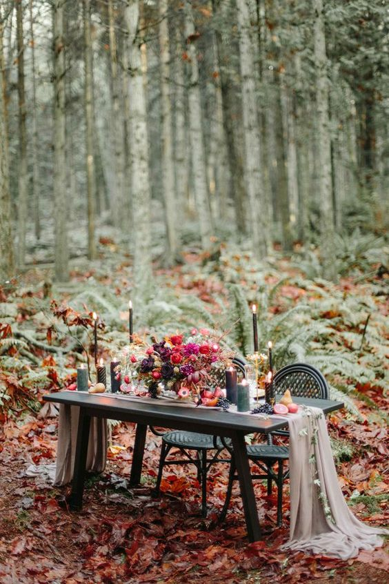 a moody woodland sweetheart table with a grey table runner, black candles and jewel toned florals