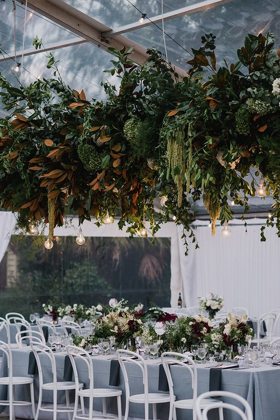 a very lush greenery wedding decoration with magnolia leaves and bulbs hanging down for a bit wild look