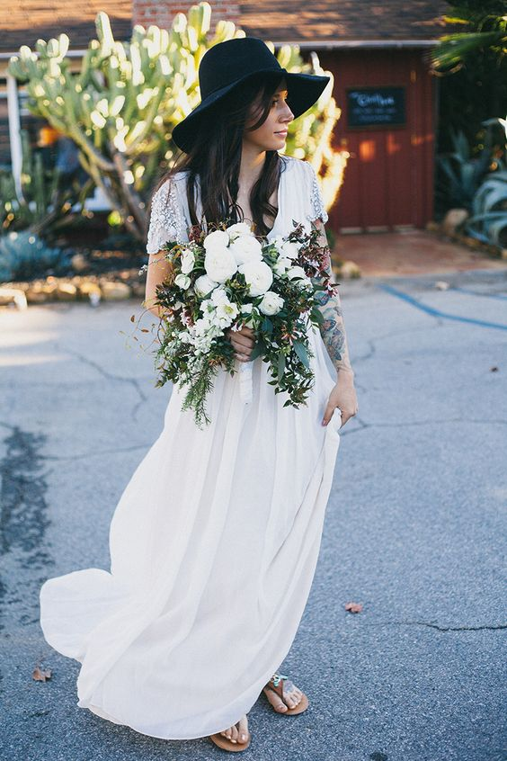 an airy and flowy embellished wedding dress, sandals and a black hat to create a bold boho look