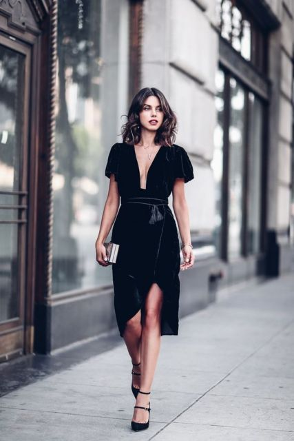 a black velvet midi dress with short sleeves and a plunging neckline, black strappy heels and a metallic clutch