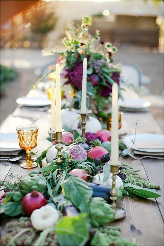 a gorgeous farm to table tablescape with a table runner of fruits and veggies plus greenery and amber glasses
