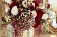 13 a luxurious floral centerpiece in the shades of ruby red, burgundy and white plus cascading blooms
