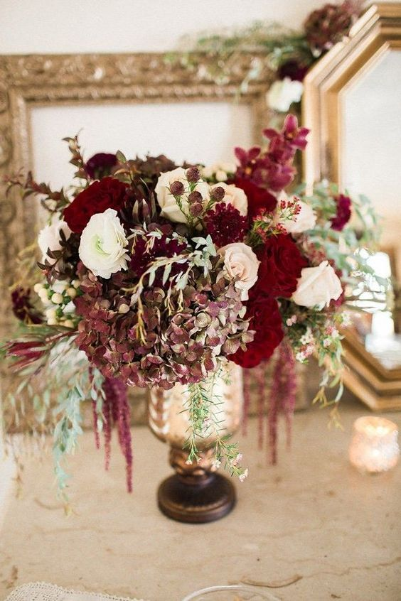 a luxurious floral centerpiece in the shades of ruby red, burgundy and white plus cascading blooms
