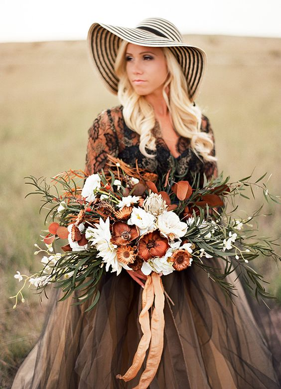 a moody wedding bouquet done in the shades of brown and rust plus white blooms and neutral ribbons