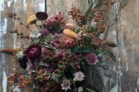 13 a moody wedding bouquet with berries, dried herbs and dark purple blooms
