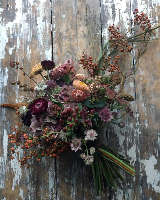 a moody wedding bouquet with berries, dried herbs and dark purple blooms