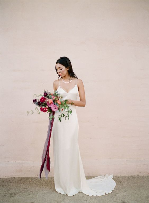 a neutral silk slip dress with a statement necklace and a train can be highlighted with a bright wedding bouquet
