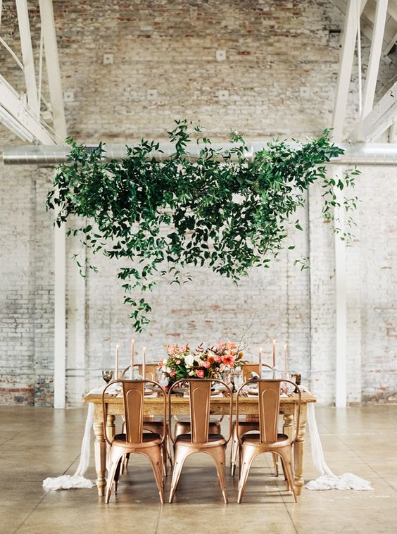 an ethereal overhead greenery decoration adds a soft touch to industrial chairs and a fresh touch