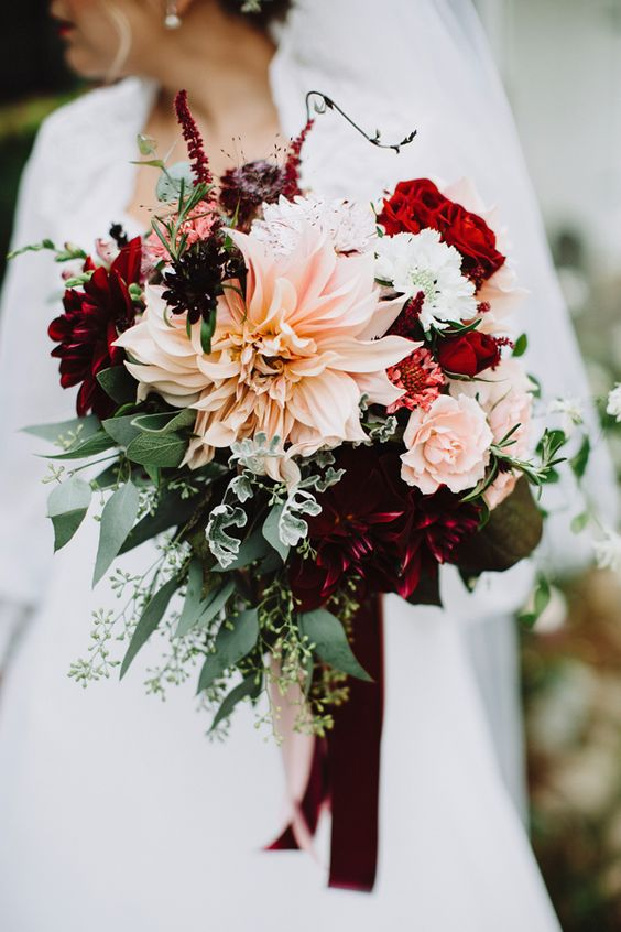 a bold bridal bouquet with hot red, burgundy and blush blooms plus textural greenery with burgundy ribbons