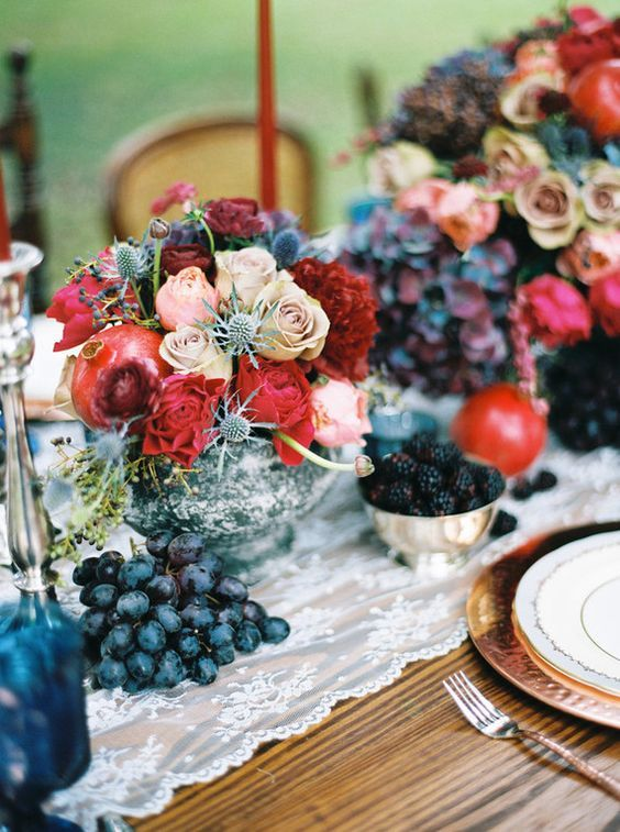 a chic jewel-tone wedding centerpiece with red and blush roses, thistles and pomegranates in a silver bowl