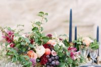 14 a lush fall centerpiece with grapes, berries and cute blooms and blue candles and plates