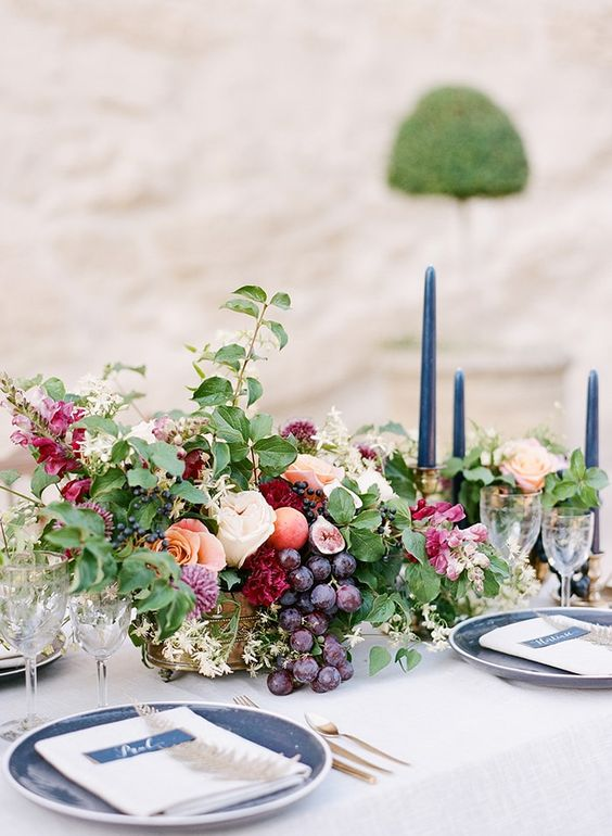 a lush fall centerpiece with grapes, berries and cute blooms and blue candles and plates