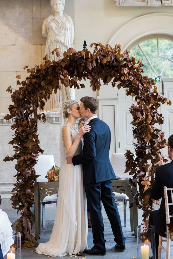 a moody fall wedding arch of dakr dried leaves looks refined and rather unusual, it's a creative way to stand out