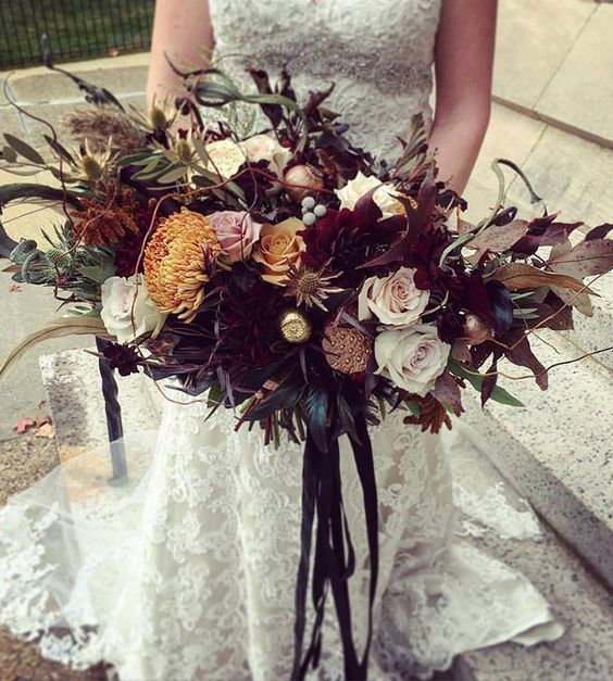 a moody lush wedding bouquet with dark foliage and blooms plus colored blooms