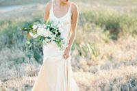 14 a neutral slip wedding dress with a side slit, a deep neckline is rocked with a red lip and a top knot