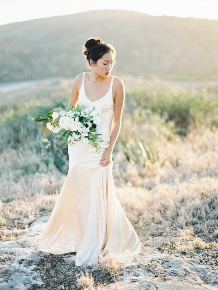 a neutral slip wedding dress with a side slit, a deep neckline is rocked with a red lip and a top knot