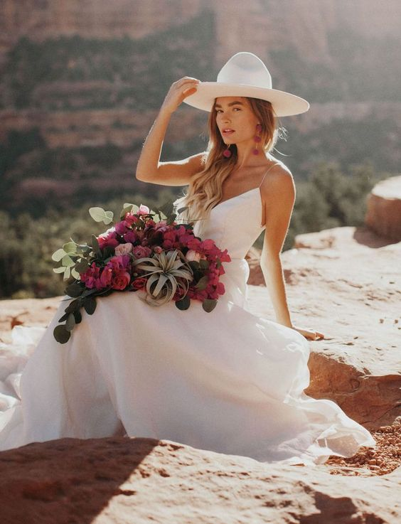 a white minimalist wedding dress on spaghetti straps and a white hat plus statement earrings