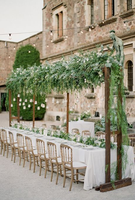 an overhead greenery decoration with white blooms and hanging candle lanterns plus a matching greeney runner