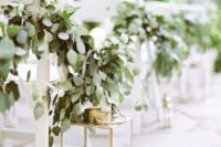 14 elegant gold candle lanterns and lush eucalyptus garlands on the chairs for a chic look