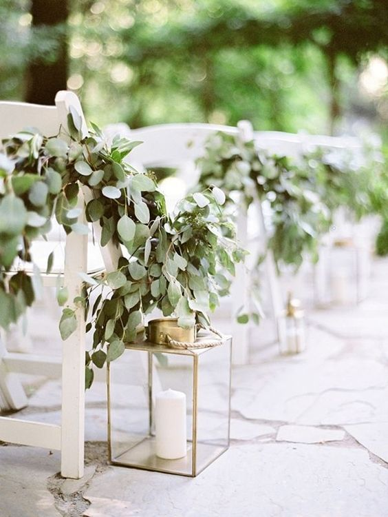 elegant gold candle lanterns and lush eucalyptus garlands on the chairs for a chic look