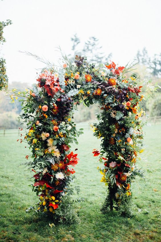 a bright fall wedding arch with red and yellow blooms, greenery, berries and fall leaves for a statement