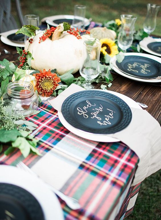 a rustic bridal shower tablescape with plaid table runners, a greenery runner with blooms, pumpkins and black chargers