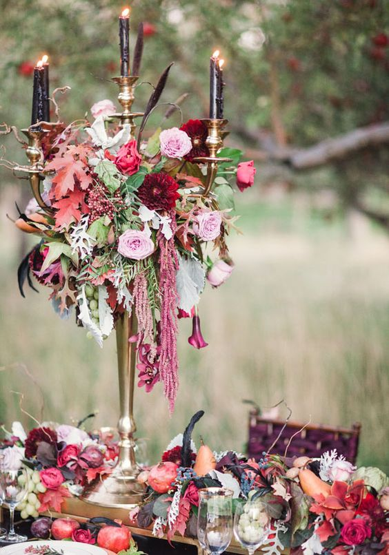 a Halloween wedding centerpiece of lush blooms, colorful leaves, cascading blooms and black candles