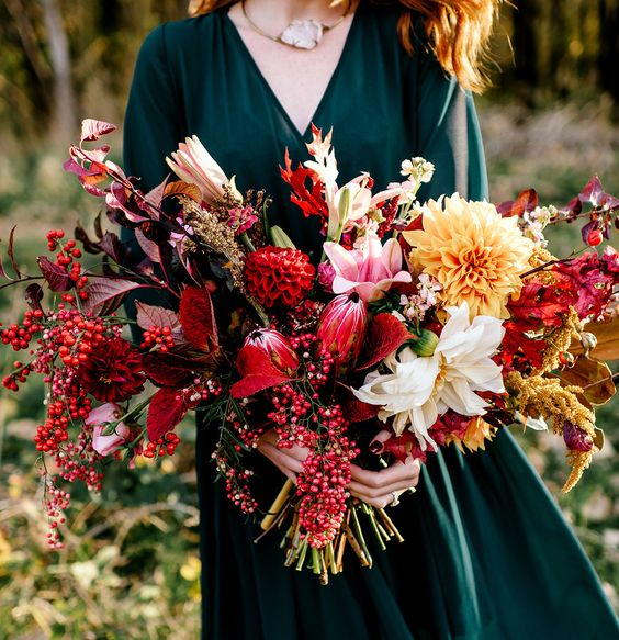 a lush and textural fall woodland wedding bouquet with colorful leaves, herbs and blooms