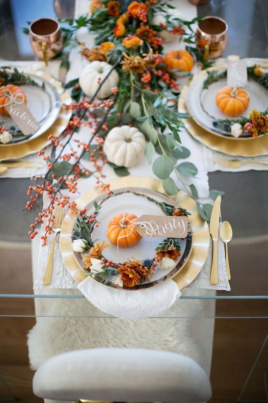 a rustic glam fall bridal shower table setting with a lucite table, bright florals, pumpkins and greenery