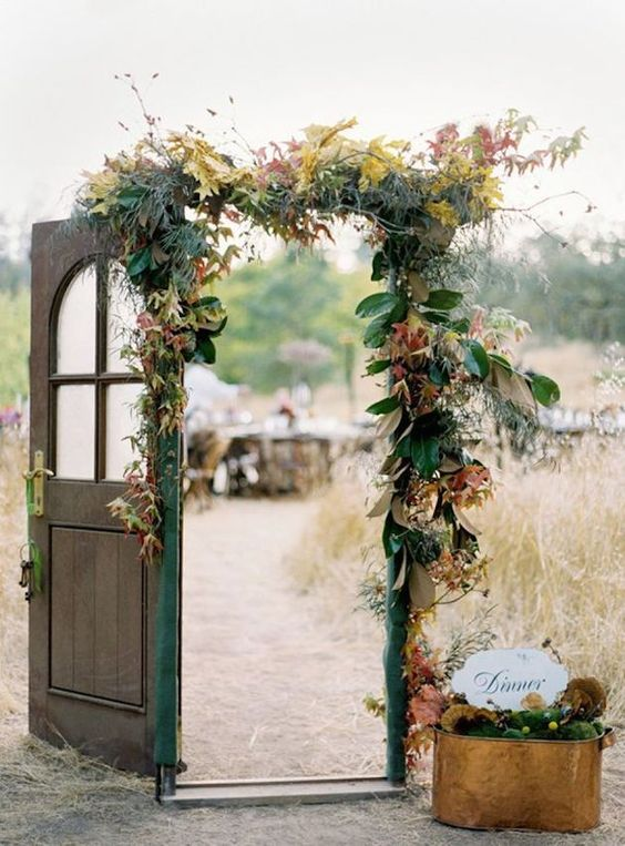 a wedding gate decorating with magnolia and colorful fall leaves and some grasses and an emerald ribbon