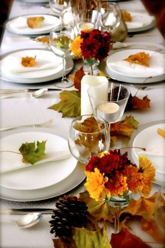 a casual wedding table setting with fall leaf runners, place markers and fall bloom centerpieces