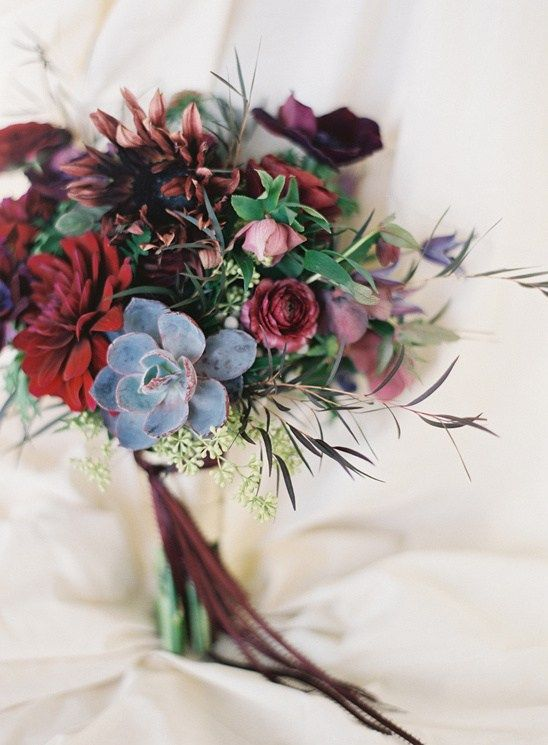 a chic moody wedding bouquet with dark blooms, pale succulents and textural greenery plus burgundy ribbons