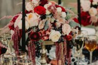 17 a lush moody wedding centerpiece of blush and red blooms, dark grapes and pomegranates plus black candles