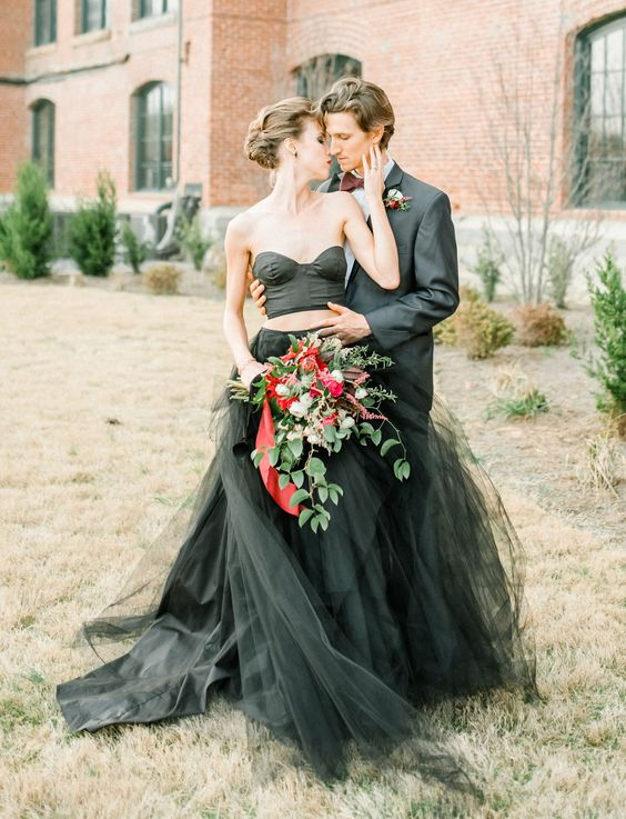 a trendy two piece black wedding dress with a strapless crop top and a layered tulle skirt