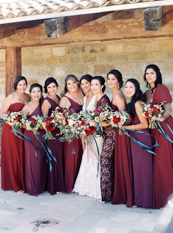 bridesmaids' dresses in the shades of red, purple, burgundy, all different and of different fabrics