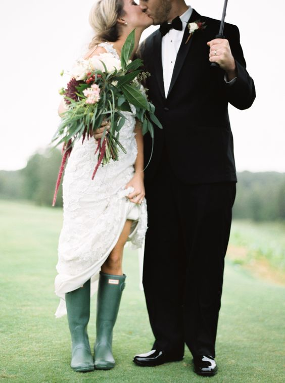 a bride wearing a lace dress, green rubber boots and a matching greenery bouquet with some blooms
