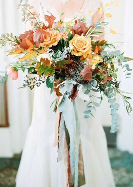 a bright wedding bouquet with cascading greenery, colorful leaves and orange flowers