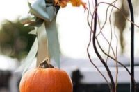 18 a cute little pumpkin with a green ribbon and leaves on a metal stand for a rustic feel
