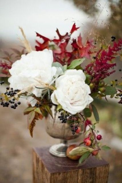 a fall wedding centerpiece with white blooms, herbs, leaves, berries and fruits in an elegant silver vase
