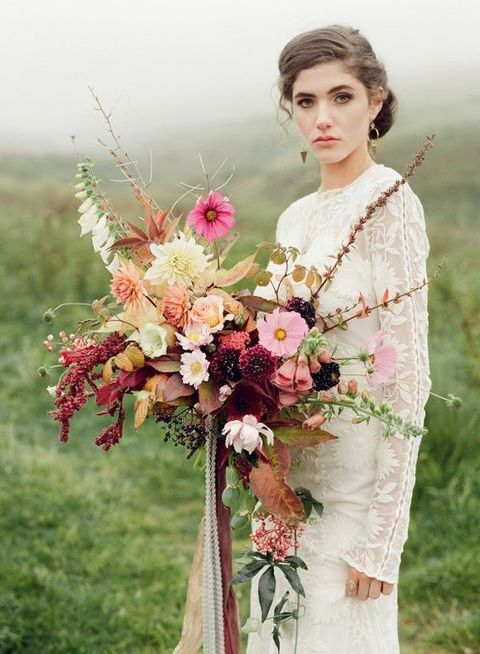a wild fall wedding bouquet with fall leaves, pink blooms and cascading greenery plus ribbons
