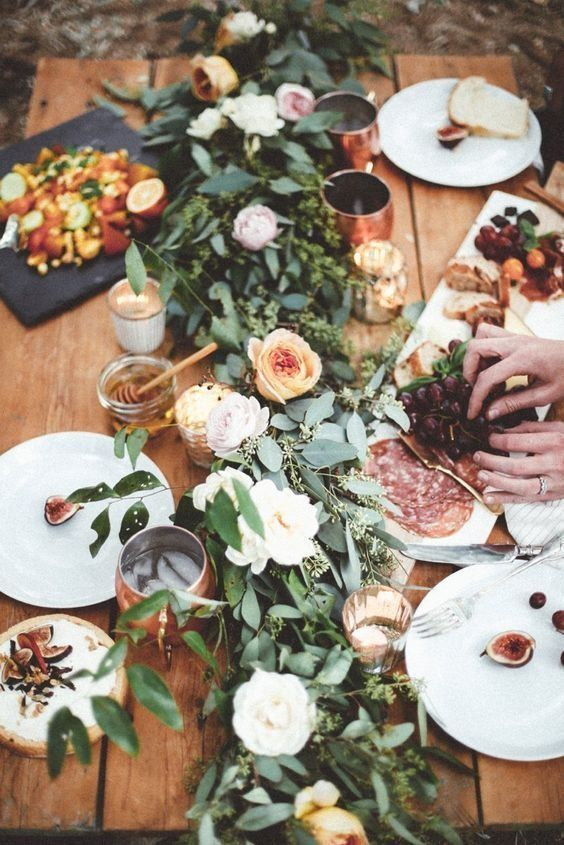 an uncovered table with a greenery runner with white and orange roses and copper mugs for the fall