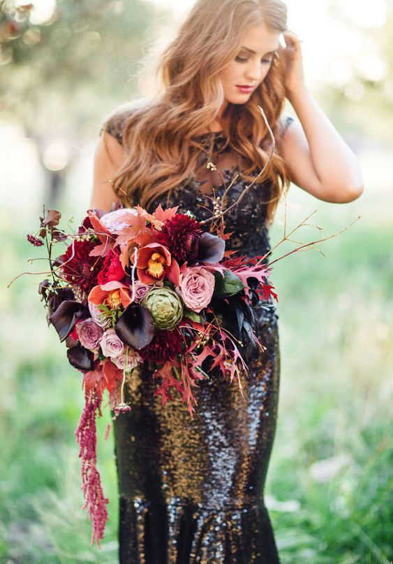 a colorful wedding bouquet with pink, hot pink and black callas plus cascading blooms and leaves