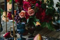 19 a moody wedding centerpiece with orange and burgundy blooms and grapes for a dark wedding