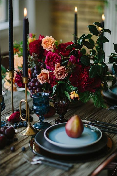 a moody wedding centerpiece with orange and burgundy blooms and grapes for a dark wedding