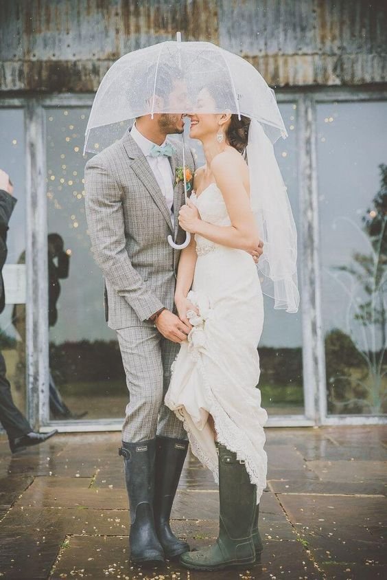 the couple wearing simple rubber boots and rocking an umbrella for some romantic outdoor pics