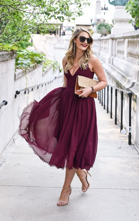a burgundy A-line midi dress with a V-neckline, a flowy skirt, nude  shoes and an embellished clutch