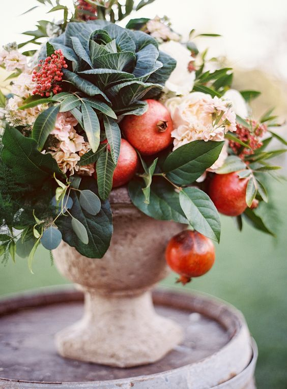 a catchy fall wedding centerpiece of blush blooms, leaves, cabbage and pomegranates in an urn