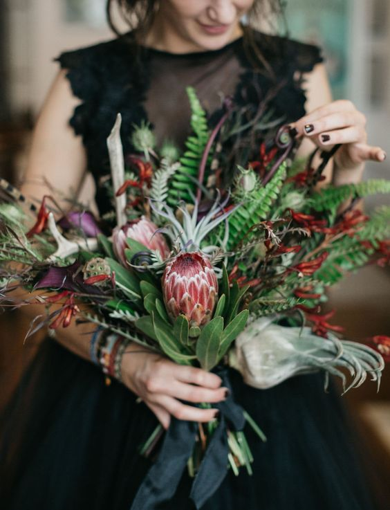 a colorful wedding bouquet with proteas, herbs and greenery plus balck ribbons
