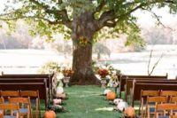 20 a rustic wedding ceremony space lined up with pumpkins and fall leaves for a cozy feel