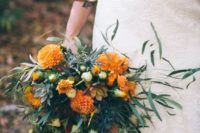 20 a whimsy two-toned bouquet of textural greenery and orange blooms plus some blue thistles